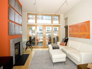 I love the open bright feel of this room. The natural light pours in and there is the perfect balance of grays, whites and oranges. The sleek gray stone fireplace  and opposing  orange accent wall and painting make for a beautiful room.