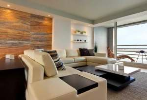 This stunning room is a simple but elegant design.  The natural wood wall provides a warm accent to the white palate and ocean view.  The darker pieces of furniture ground the room which is also highlighted by the custom lighting.