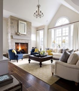 This beautiful room is flooded with amazing natural light.  It's architecturally detailed windows are framed with neutral draperies.  The natural furniture complements the contrasting coffee table, fireplace, drapery rod, accent chair and pillows.  The lighting fixture above provides a focal point bringing  your eye around the room.